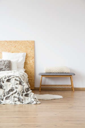 White knit blanket on bench next to bed with patterned bedsheets in natural bedroom with copy space