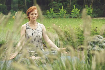 Woman with red hair meditating in a meadow in lotus position
