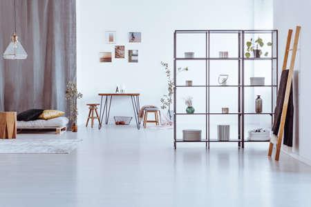 Escalera de madera y mesa contra una pared con galería en espacio abierto con estantes, lámpara encima de taburete y cama Foto de archivo