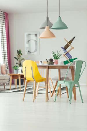 ランプ、ミント、黄色の椅子付きのダイニングルームのインテリアの木製テーブルのラックとケトルのボトル
