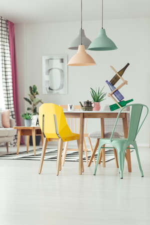 Bottles on rack and kettle on wooden table in dining room interior with lamps and mint and yellow chair Stockfoto