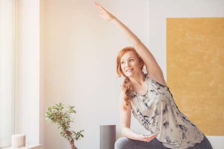 Smiling ginger woman practicing yoga by the window in a bright room with a plant