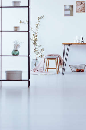 Shelves with boxes in white dining room with photos above table and stool near vase with branch Banque d'images