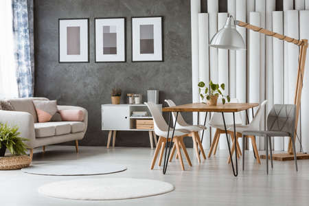 Bright dining room with white plastic chairs and relax space with beige couch and pink cushions Banque d'images