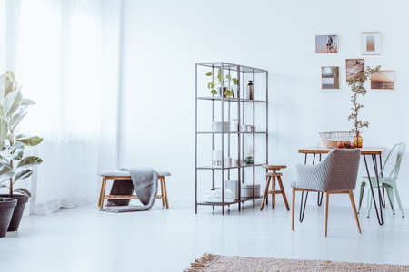 Chairs and stool at dining table with vase against white wall with photos, shelves and bench in bright interior