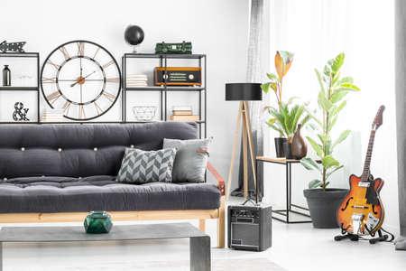 남자의 거실에 테이블의 앞에 어두운 settee에 회색 베개 벽에 기타와 디자이너 시계와 인테리어 스톡 콘텐츠