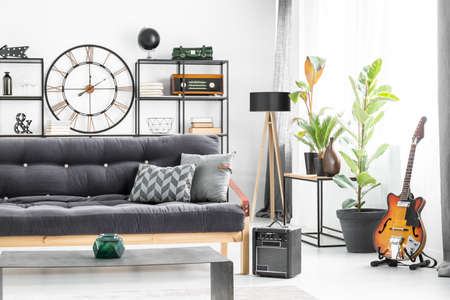 Grey pillows on dark settee in front of a table in man's living room interior with guitar and designer clock on the wall