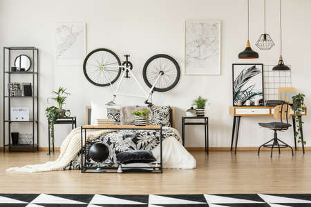 White bike in the middle of open space bedroom with workspace and botanic bedsheets Banque d'images