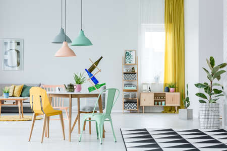 Plant on geometric carpet and rustic cupboard in cozy living room interior with yellow and mint chair at table under pastel lamps