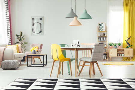 Alfombra geométrica en el acogedor interior de la sala de estar con lámparas en colores pastel sobre la mesa de madera y silla amarilla, menta y gris contra una pared con cartel