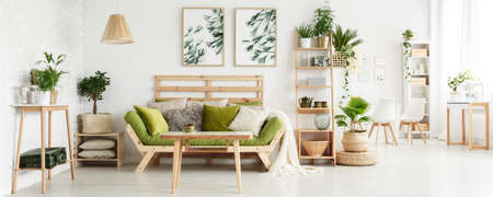 Wooden table in front of green couch with cushions in floral living room interior with leaves posters and suitcase on shelf Banque d'images