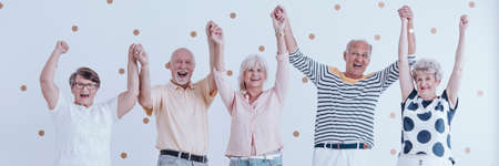 Group of happy senior friends having fun together during party and holding hands