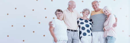 Enthusiastic elderly friends celebrating their meeting against white wallpaper with gold dots Banque d'images