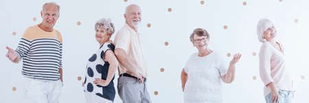 Smiling senior friends posing and enjoying retirement together. White wall with gold dots in the background