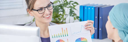 Businesswoman showing charts regarding chemotherapy effects to woman with cancer