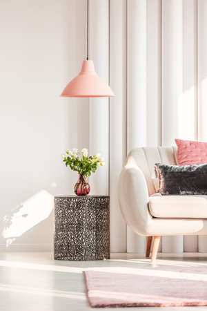 White sofa next to metal table with roses in bright living room interior design