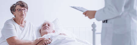 Suffering senior man looking at his worried wife asking the doctor about the condition of his health