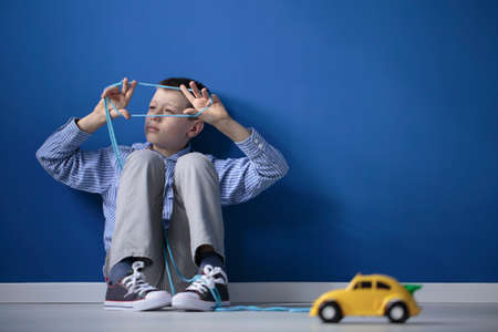 Autistic child playing with a string and a yellow toy car against a blue wall with copy space
