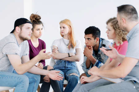 Multicultural group of young people brainstorming during therapy with counselor
