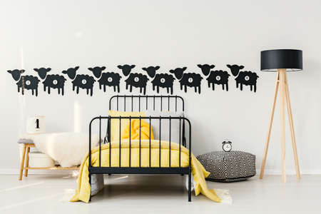 Yellow bedsheets on babys bed between lamp, pouf with clock and bench with white fur in bedroom interior with black sheep stickers on the wall Stock Photo