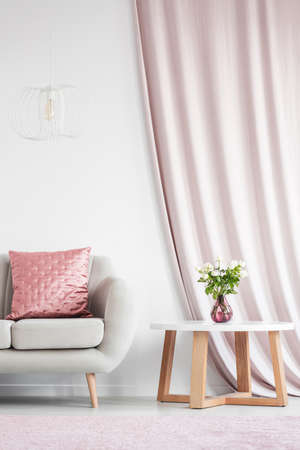 White lamp above beige sofa with pink cushion in white living room interior with pink curtain