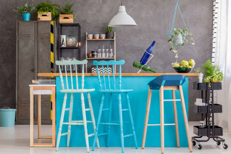 Wooden barstools standing at turquoise kitchen island in bright dining room interior with gray wall Banque d'images