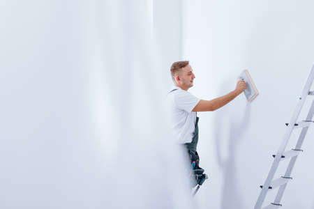 handyman cleaning white wall using wiper during finishing interior with ladder Stock Photo