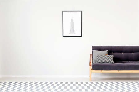 Grey cushions on wooden black sofa against a wall with copy space and poster in bright living room interior with patterned carpet