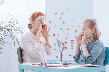 Young blonde girl learning to speak properly with elder therapist in glasses
