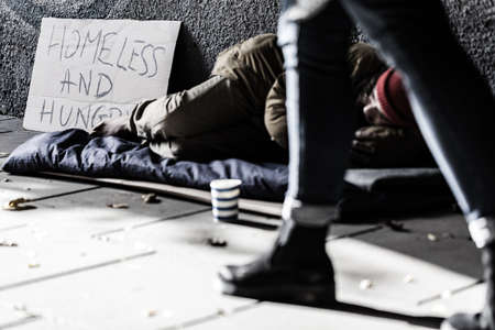 street person in sleeping-bag begging for money and food Reklamní fotografie - 93533383
