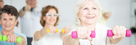 Smiling senior woman lifting pink dumbbells with elderly friends at the gym Banque d'images