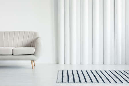 Beige sofa in white living room interior with striped rug and tubes wall with copy space