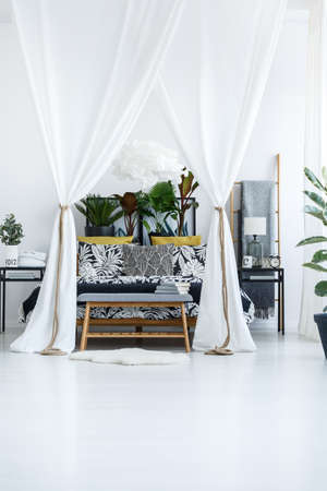 White marquees above bed with plants on the bedhead in bright bedroom interior with wooden bench and rug