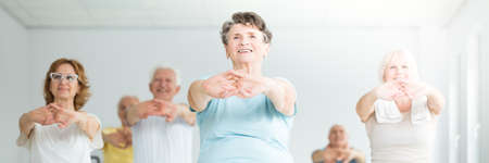 Low angle of smiling elderly woman stretching with a group of senior people in a yoga center