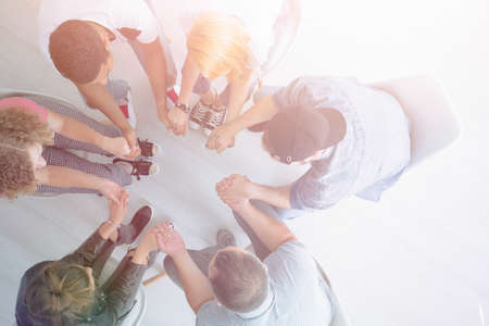 High angle of young people holding hands and sitting in a circle during group therapy