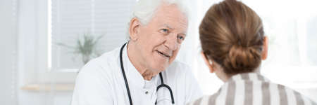Professional senior doctor consulting tests results with patient