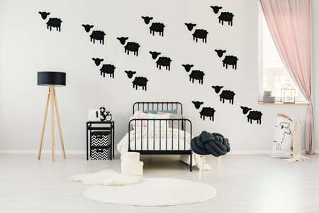 White rugs next to child's bed against a wall with black sheep stickers in black and white bedroom interior with wooden lamp and stool