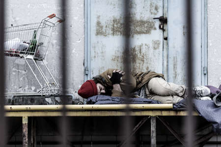 tired homeless man sleeping on a blanket on a city street Banque d'images