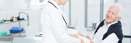 Smiling elderly patient thanking doctor in white uniform for healthcare and bandaging his hand
