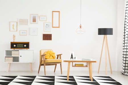Wooden table on black and white carpet near lamp and vintage armchair with yellow pillow in bright apartment interior with radio on cupboard against wall with posters Banque d'images