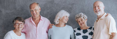 Smiling elderly people enjoying their friendship, standing against concrete wall Banque d'images