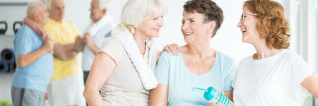 Happy elderly women smiling and talking during a break between classes in a fitness studio