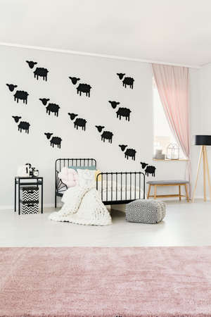 Patterned pouf, pink carpet and white knit blanket on bed in bright kids bedroom interior with sheep wall stickers and grey bench Banque d'images