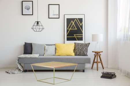Simple living room interior with yellow cushion lying on a gray couch and gold table near the window