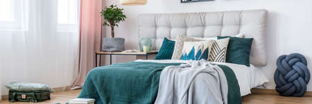 Blue knot pillow next to bed with grey and green bedding in bedroom interior with plant and suitcase
