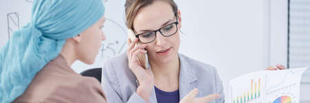 Businesswoman talking on the phone during meeting with woman with cancer wearing blue scarf Banque d'images