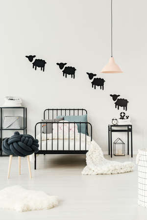 White fur next to a stool and kids bed with blanket under pastel lamp in bedroom interior with clock on nightstand against a wall with black sheep stickers