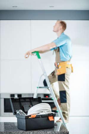 台所の照明を修理するはしごの上のカウンターと電気技師の黒い用具箱