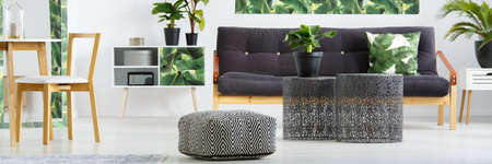 Patterned pouf and metal tables with plant in floral living room interior with wooden chair, dark settee and pillow