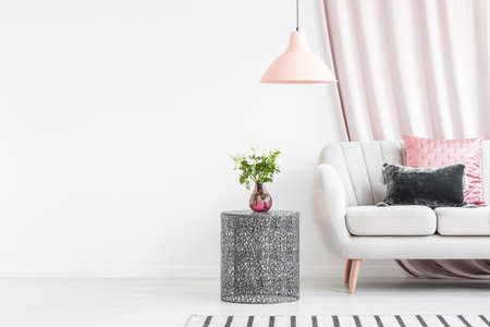 Roses on black table next to bright sofa with cushions in living room interior with empty wall Stockfoto
